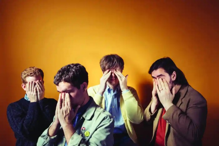 Parquet Courts stand together, all with their heads in their hands, rubbing their eyes. The background is a dark brown in the corners of the image and fades to a light orange in the centre.