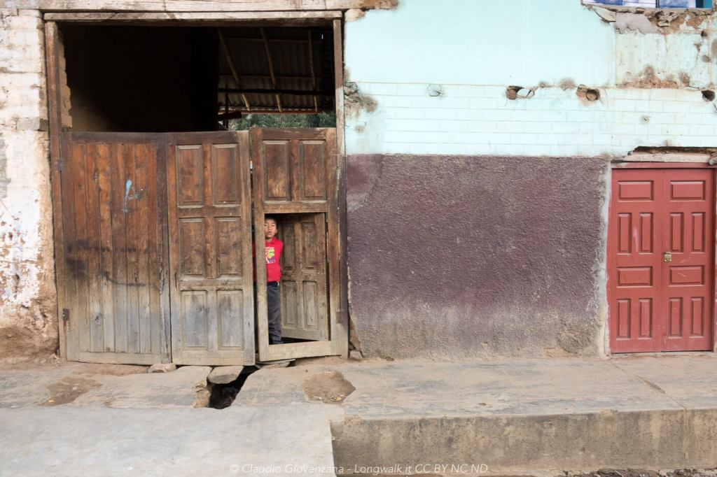 un bambino peruviano fa capolino fuori dalla porta