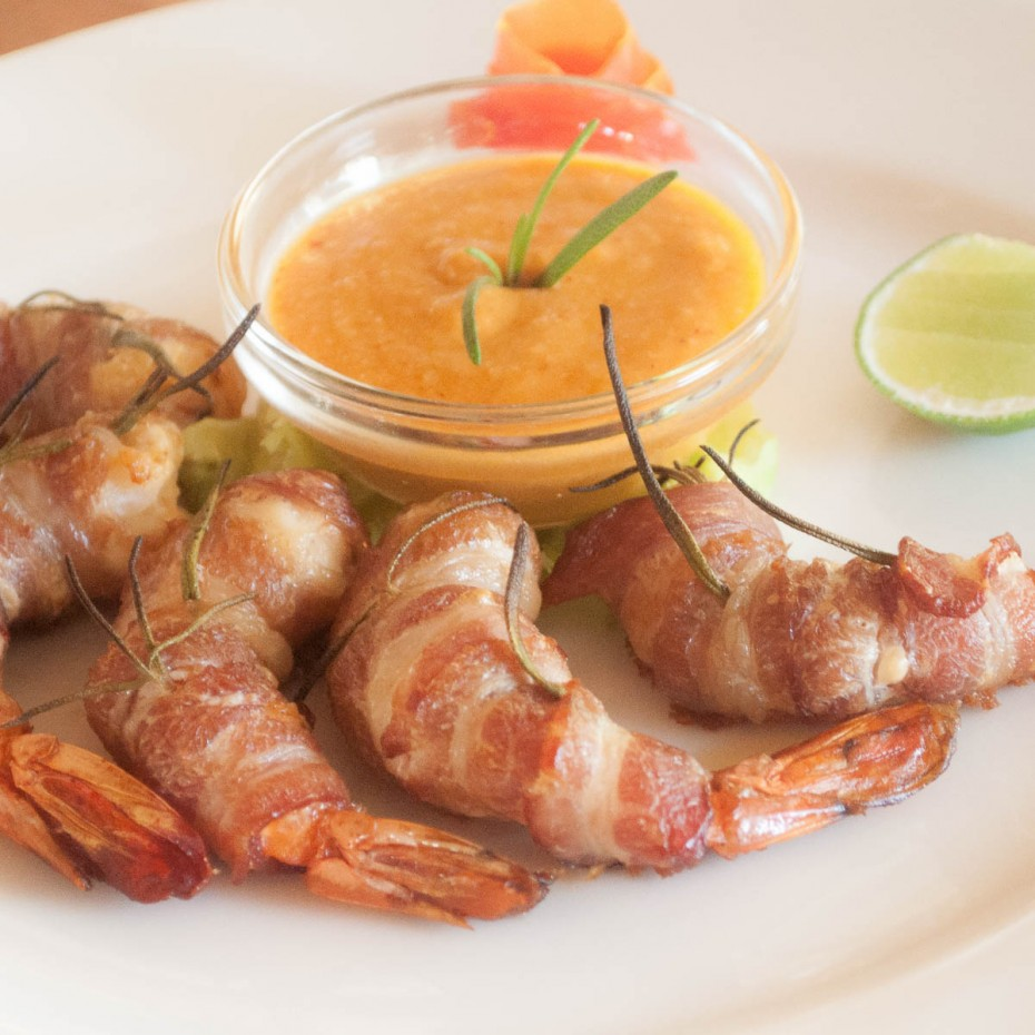 Prawns wrapped in streaky bacon, with rosemary, baked in the oven and served with mashed chickpeas