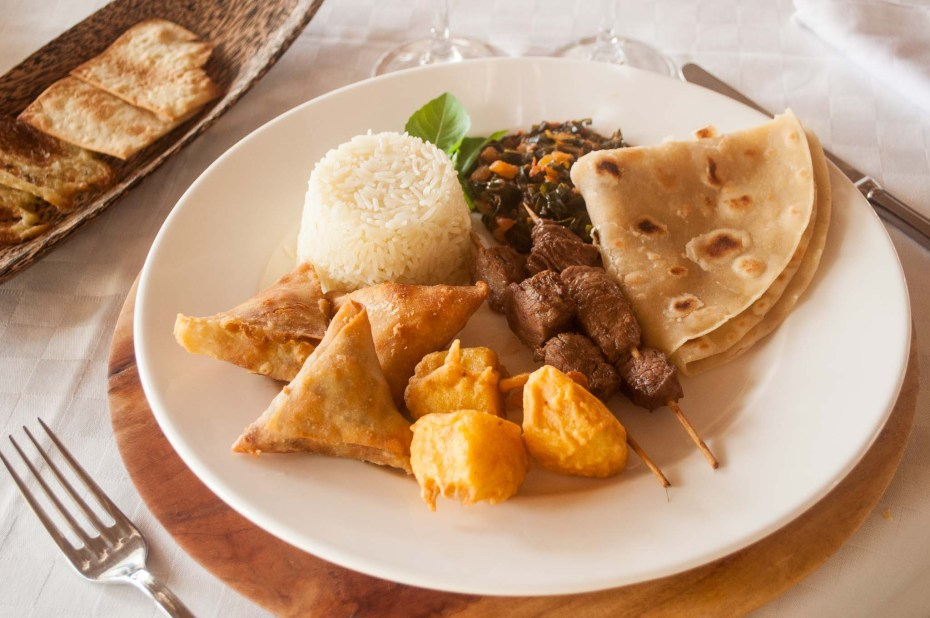 Lonno swahili dish With mixed samosa (feta and tomatoes, meat, vegetables), coconut rice, battered potatoes, sukuma wiki (local vegetable), chapati (local bread) and mi