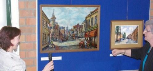 Voorzitter Corrie Hoekstra-van Vuurde legt aan Selma Kers de betekenis van dit kruispunt uit; het Loosduinse Hoofdplein. Het centrum van de dorpskern waar vier hoofdstraten bijeenkomen. Geschilderd vanuit de Emmastraat (nu Loosduinse Hoofdstraat), de bibliotheek. Rechts was de Kijkduinsestraat (nu Arnold Spoelstraat). Links is de Willem III straat.