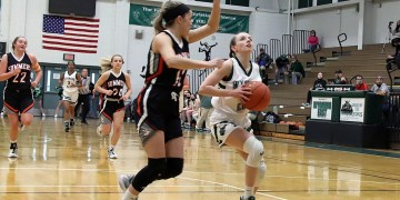 Wyoming East's Abby Russell (right) drives to the basket against Summers County's Taylor Isaac during the Class AA Region 3, Section 1 championship on April 16 in New Richmond. (Photo: Jim Cook)