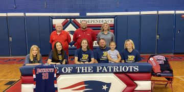 """Emily Suddreth (first row, center) is surrounded by coaches and family as she signs to continue her career at Bluefield State. Pictured (from left to right) in the bottom row is Abigail Suddreth, Daphne Suddreth, Emily Suddreth, Keith Suddreth, Kynlee Suddreth and Kennedy James. Pictured in the back row (from left to right) is Independence assistant coach David """"Scotty"""" Cuthbert, Head Coach Mark Cuthbert, and assistant coach Kayla Hart. (Submitted Photo)"""