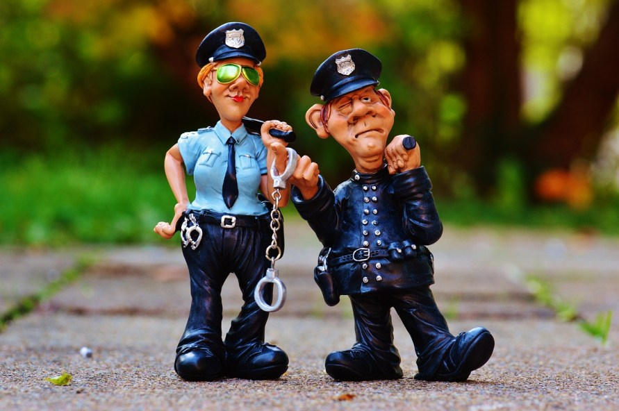Two funny looking police figurines stand cuffed to each other.