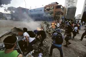 Anti-government protesters stand behind a barricade during clashes at Altamira square in Caracas