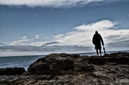 Uomo con ombrello sul mare