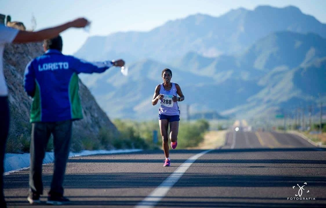 Half marathon Kenyan girl competitor on highway one