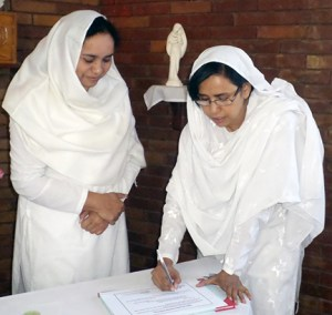 From left, Nasreen Daniel looks on as her sister Maria Daniel signs her vow renewal. Nasreen acted as a delegate for Loretto President Pearl McGivney to receive the vows of Maria and Samina. (Photo courtesy of Pakistan Sisters)