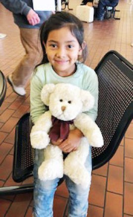 A young girl at the bus station hugs her teddy bear. (Photo courtesy of the Rev. Jim Flynn)
