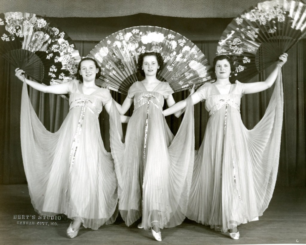 Three female students pose before their dance recital