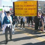 Loretto Community members march with yellow banner in the Denver Marade