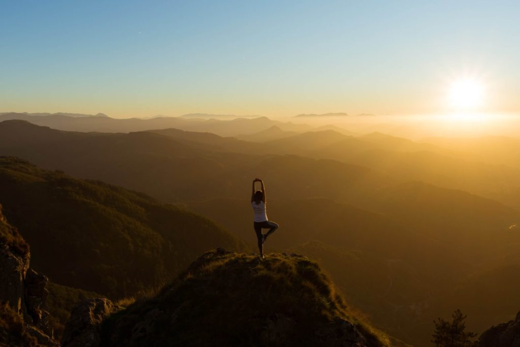 a woman doing yoga at sunrise in the mountains