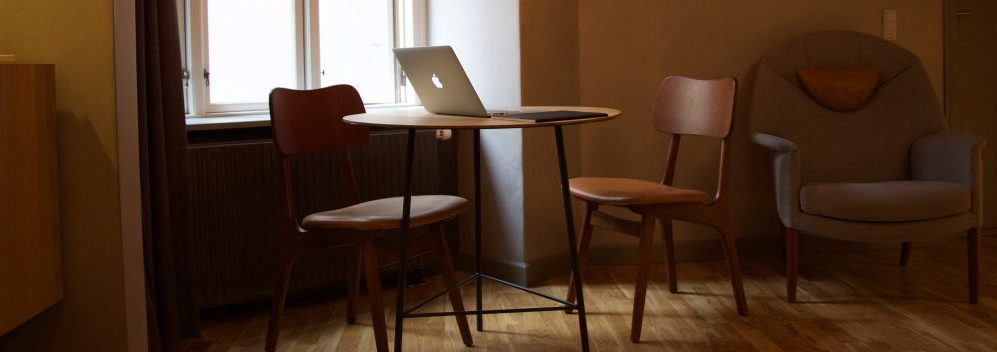 Two chairs at a round table in a cafe, with a laptop on the table.