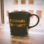 "Black mug with the words ""eternal optimist"" in gold."