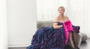 Bonnie Masina in a lavish, purple flamenco dress, seated on a couch.
