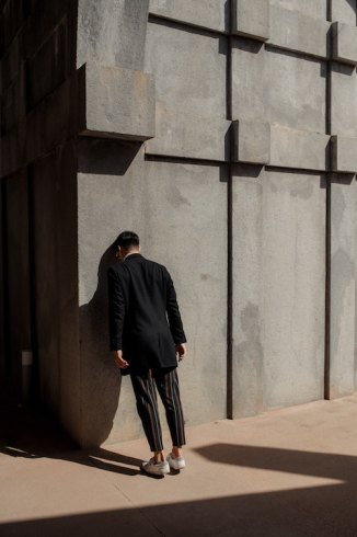 Man in dark clothing leaning with his forehead against a cement wall.