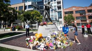 Fans have placed flowers and other tributes at the base of Tony Gwynn's statue at Petco Park. (AP)