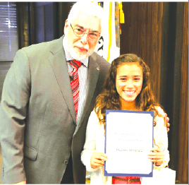 "La Mirada Mayor Steve De Ruse presents 7th grade student Madeline Hernandez of St. Paul of the Cross with a certificate of recognition for winning 1st Place in her age group for the annual ""Love a Tree"" Poster Contest."