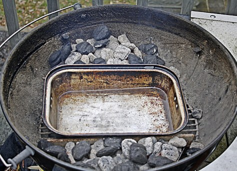 The coals are divided on each side of the kettle and a small roasting pan is placed in the middle to catch the drippings. A layer of water helps keep the drippings from scorching.