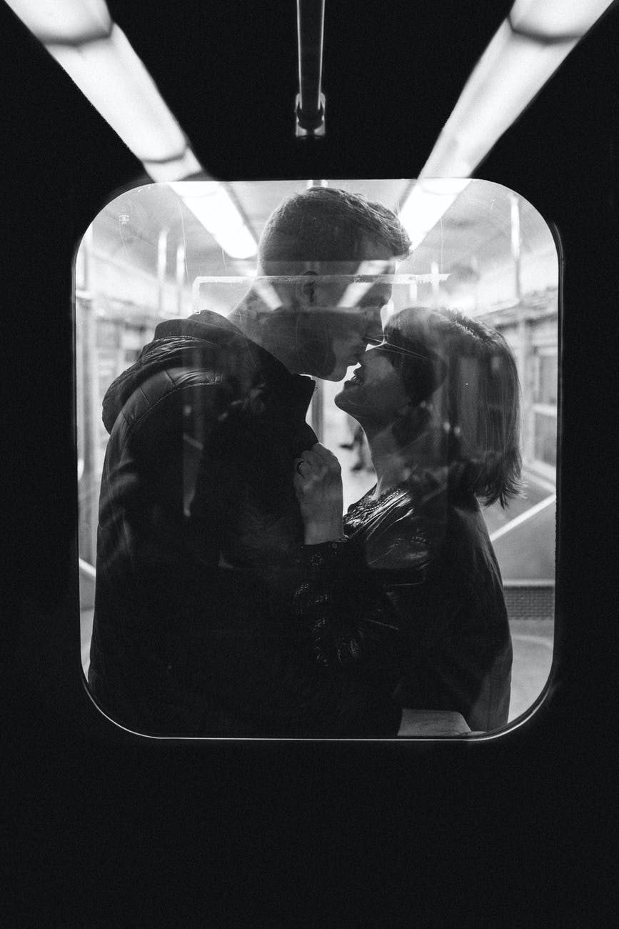 grayscale photo of man kissing woman s nose while standing inside a train