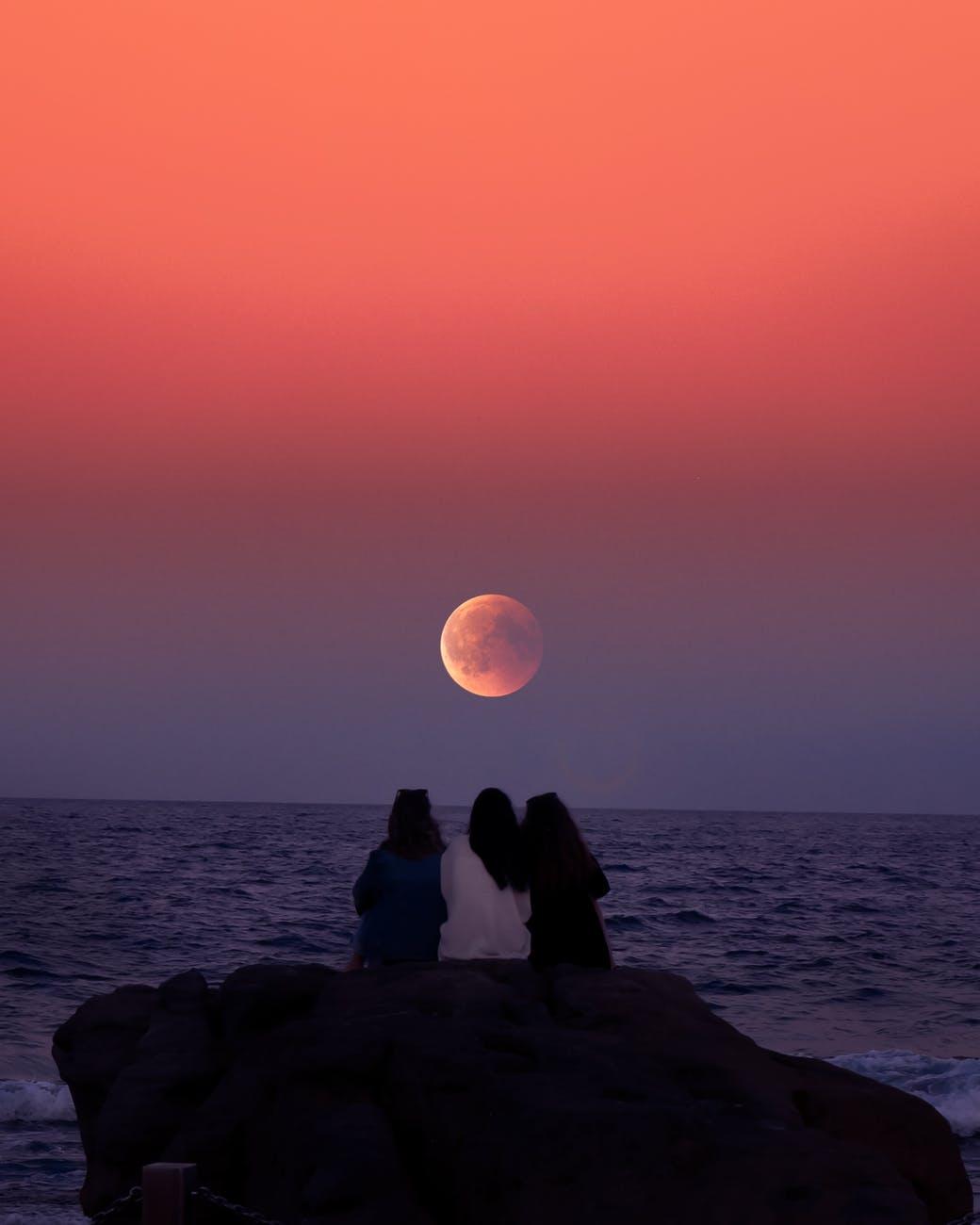 three women sitting on rock infront of ocean