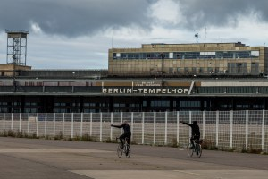 Berlin Tempelhof Field with two bikers in black with left arm raised