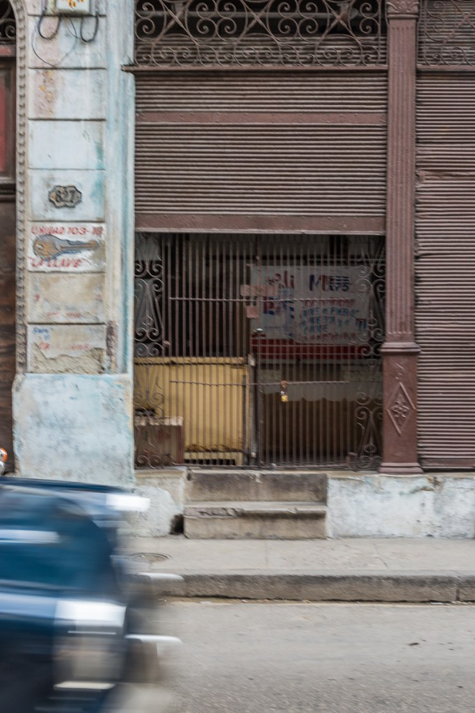 View of a old American car driving by the exterior of a building in Havana Cuba | LOST NOT FOUND| La Habana | Cuba | Havana | Street Photography