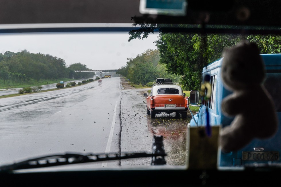 View of old cars on the side of the road from inside a car in Cuba | LOST NOT FOUND | Cuba | Street Photography