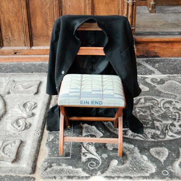 Christian Boltanski - Attente - 15 stoelen met 15 jassen