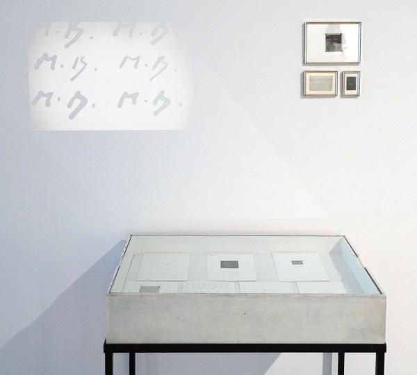 Marcel Broodthaers - La Signature de l'Artiste - INgelijste filmnegetieven met schriftuur, diaprojectie, vitrine op tafel en 7 handgeschreven vellen papier