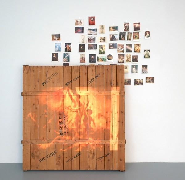 Marcel Broodthaers - Projection zur caisse - 50 35mm dia's geprojecteerd op verpakkingskist met prentkaarten op muur