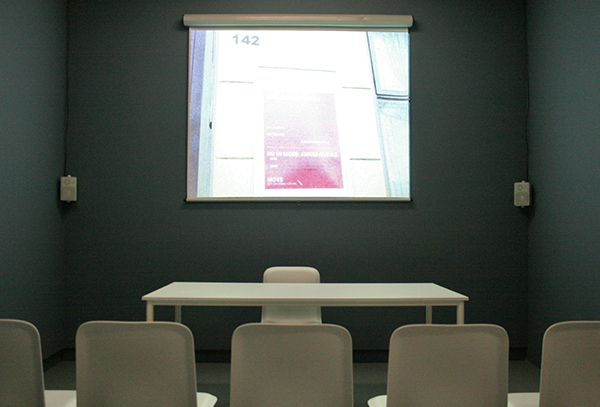 Judith Deschamps - A Talk to the Leftovers - Installatie, nagebouwde versie van een ruimte met stoelen, tafel, beamer, speaker en foto's