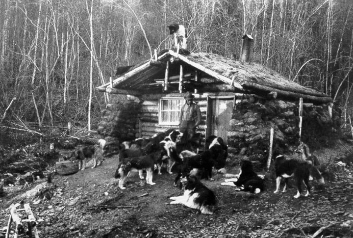 Black and white image of a man in front of log cabin surrounded by dogs