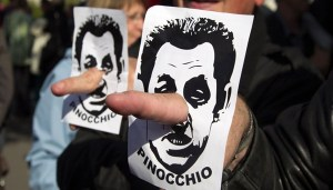 A demonstrator use fingers in the place of the nose with an image of Sarkozy, France's President and UMP party candidate for the 2012 French presidential election, referring to him as Pinocchio during the traditional labour union Labour Day march in Paris