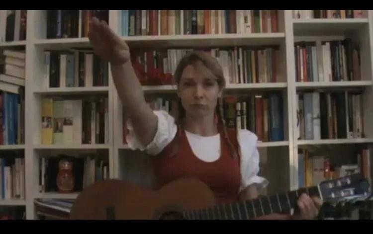 Maria Stern zeigt in YouTube-Video den Hitlergruß (Screenshot), sie sitzt mit Gitarre vor einer Bücherwand und trägt Dirndl