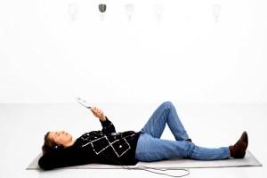 Bild på Louise Blad som ligger på ett grått liggunderlag framför en vit vägg. Louise har ett par hörlurar på sig och håller i en handspegel. På väggen bakom henne hänger ytterligare sex stycken handspeglar. Foto: Jean-Baptiste Bèranger.