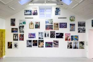 Bild på en vägg fylld av vykort uppförstorade till posters. Dear Jackie – Postcards as Posters Galleri Mejan, 2014 Foto: Jean Baptiste Béranger.