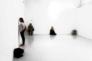 Tre personer befinner sig i ett helt vitt rum. En person sitter lutat mot väggen, en sitter på en trappa och en står med näsan mot väggen. Foto: Calle Holck.