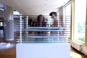 Bild på glas i olika nivår som det ligger tre pappersark på. Bakom ställningen står två personer. Foto: Calle Holck.