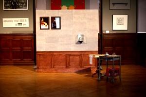Startpunkt av guidning. En tillfällig vägg med tapet och trädekor längst ned. Bredvid står två bord. På nedervåningen på ett av borden står det en röd glasflasklåda. Foto: Calle Holck
