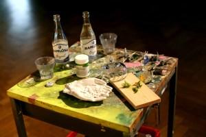 Detalj startpunkt. Bild på ett av borden vid startpunkten. På bordet finns många saker, bland annat två Ramlösa-flaskor, två glas, en burk, en gipshand, en skärbräda... mm. Foto: Calle Holck