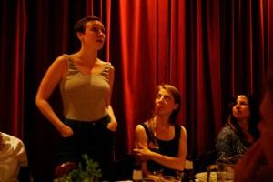 Bild på tre personer på middagsbjudning. En person står upp. Bakom dem hänger ett rött sammetsdraperi. Foto: Eva Mag
