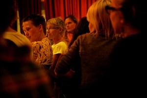 Bild på ca 8 personer som sitter på middagsbjudning med ett rött sammetsdraperi bakom. Foto: Eva Mag