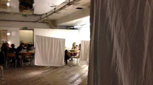 X;;3⁄5jfh&÷gF#.v?qvö© Bild på en grupp personer längst bort i vänstra hörnet. Framför dem hänger flertalet vita tyger på tvättlinor.