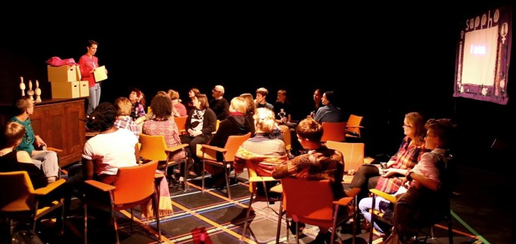 Performance, PotatoPotato, 2015. Louise står framför en grupp personer som sitter på stolar. Bredvid sig har hon flertalet kartonger.