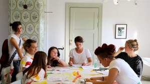 Esters äpplen -Esters äpplen - Sju personer sitter runt ett bord med tyger som har färgglada streck på sig. Foto: Calle Holck
