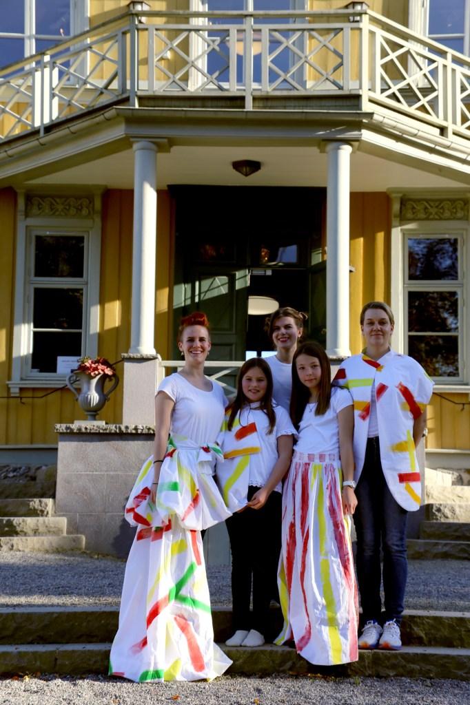 Fem personer tar ett gruppfoto framför en gul villa. De har kläder med färgglada streck på sig. Foto: Calle Holck