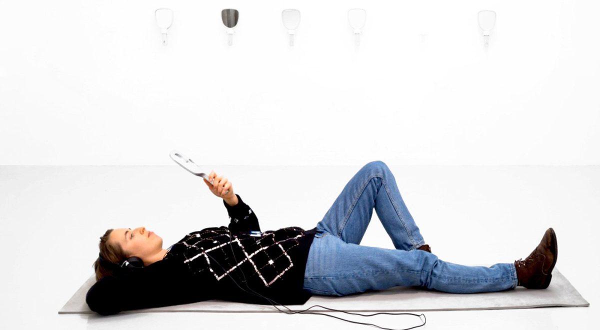 Walls are Painted White / Ensammast i Sverige. Bild på Louise Blad som ligger på ett grått liggunderlag framför en vit vägg. Louise har ett par hörlurar på sig och håller i en handspegel. På väggen bakom henne hänger ytterligare sex stycken handspeglar. Foto: Jean-Baptiste Bèranger.