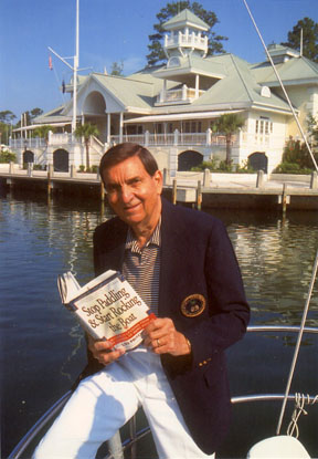 Lou Pritchett on a yacht, holding his book, which has nothing to do with politics. Notice the lack of libraries in the photo.