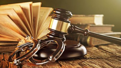 An image of a gavel, handcuffs, and books